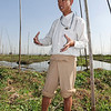 KOKO, OUR WONDERFUL GUIDE, STANDS ON ONE OF THE FLOATING ISLANDS, WHERE MANY CROPS ARE GROWN. HIS FEET SINK INTO THE WATER.