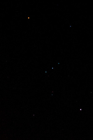 Orion.  Out of focus so that the colours show up.  Betelgeuse (top left) is a red giant.  Rigel (bottom right) much hotter but smaller so blue-violet.