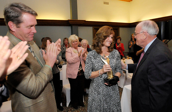 Stephanie Moran receives the Athena 2012 award from The Herald Bulletin Publisher Henry Bird as her husband Mike looks on during the Athena and Community Shining Star Awards Gala at the Anderson Country Club on Tuesday.