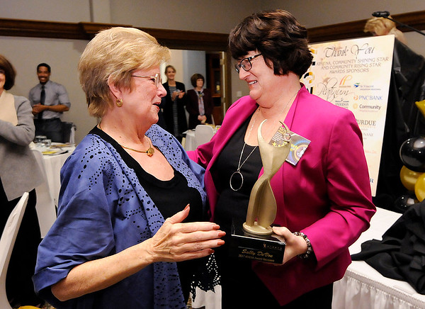 Don Knight |  The Herald Bulletin<br /> Sally DeVoe receives her Athena award from The Herald Bulletin Publisher Beverly Joyce during the Athena awards dinner at the Anderson Country Club on Thursday.