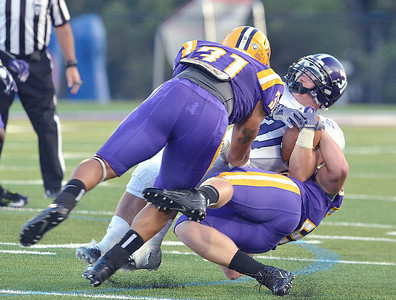 J.S.Carras/DIgitalfirstmedia.com  Holy Cross ball carrier Gabe Guild is tackled by UAlbany's Kyle Jordan (31) and John Forster during second quarter of college football action Saturday, August 30, 2014 at Bob Ford Field at UAlbany in Albany, N.Y..