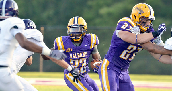 J.S.Carras/DIgitalfirstmedia.com  UAlbany ball carrier Omar Osbourne (23) follows block by teammate Nic Ketter (21) against Holy Cross during second quarter of college football action Saturday, August 30, 2014 at Bob Ford Field at UAlbany in Albany, N.Y..