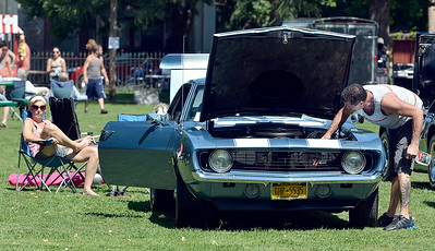 J.S.Carras/The Saratogian  Casey Bobb enjoys sunshine while her husband Thomas Bobb of Nassau cleans up his 1969 Chevy Z-28 302 during Uncle Sam Jam and Car Show Saturday, August 30, 2014 at  Powers Park in Troy, N.Y..