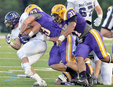 J.S.Carras/DIgitalfirstmedia.com  Holy Cross ball carrier Gabe Guild (31) is tackled by UAlbany's Kyle Jordan (31) and John Forster (93) during second quarter of college football action Saturday, August 30, 2014 at Bob Ford Field at UAlbany in Albany, N.Y..