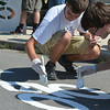 "Pitt-Johnstown freshmen Ben Blemmer (left) and Gregory Dederer fill in a ""Share the Road"" stencil Saturday along Somerset Street in Johnstown. 85 students were bused downtown to help as part of the college's orientation."