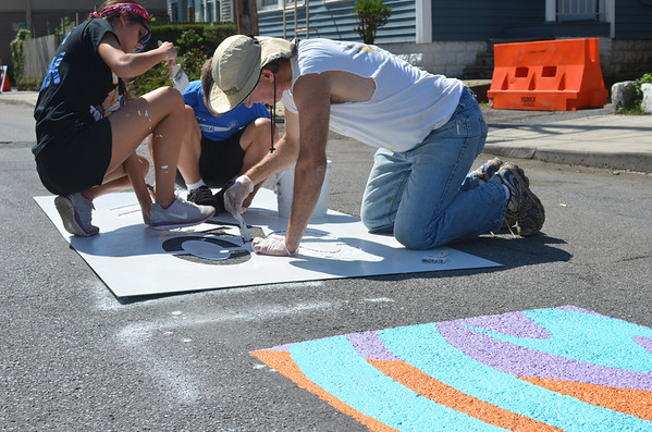 """Dan March (right), Katie Saylor and her brother Nick Saylor fill in a """"Share the Road"""" stencil Saturday along Somerset Street in Johnstown. Nearly 100 volunteers from Pitt-Johnstown, local rotary clubs and a Mennonite volunteer group gathered to beautify the area through trash pickup, weed-pulling and painting stencils that promote awareness of cyclists."""