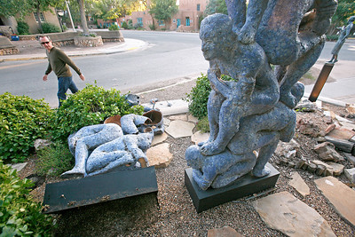 """A man walks by and see a ceramic sculpture entitled """"Blue Gate"""" by artist Mark Chatterley laying shattered at about 7:00 p.m. in front of The Edge gallery on the corner of Canyon Road and Paseo de Peralta on Aug. 24, 2010.             Luis Sanchez Saturno/ The New Mexican."""