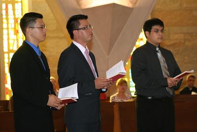 Son Ho, Luis Fernando Orozco Cardona and Joseph Vu hold the Rule of Life.