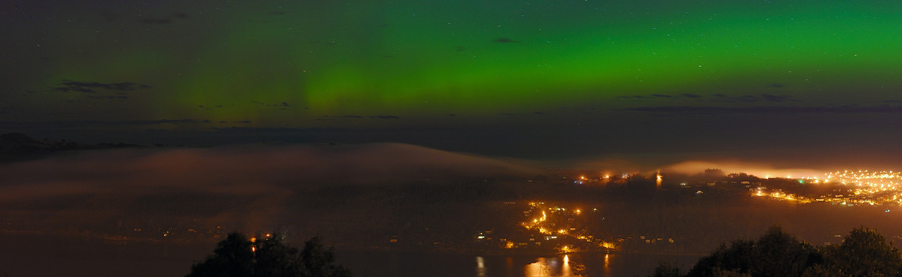 Otago Penisula sleeps under a layer of fog, while the aurora australis shines in the sky above. Signal Hill, Dunedin, 16 July 2012, 1:16am