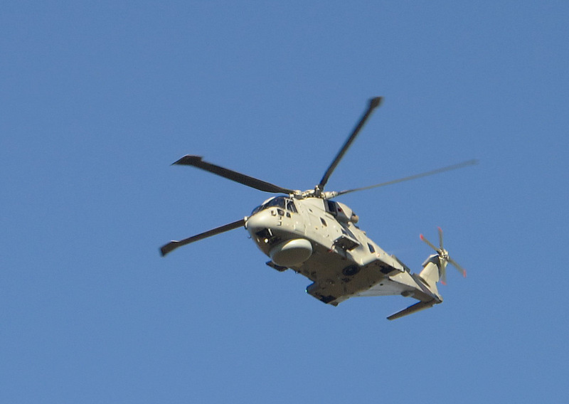 A Royal Navy Merlin helicopter passes fast and low.