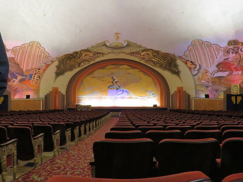 "The Avalon Theatre.   The asbestos safety curtain's design is called ""Flight of Fancy"" which depicts a primitive surfer boy riding a wave superimposed on the map of Catalina.  Above is a re-creation of Botticelli's ""Birth of Venus."""