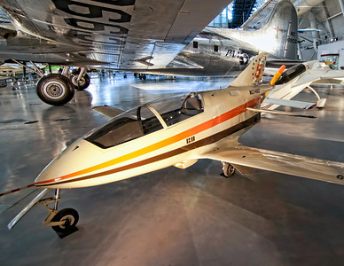 """Bede BD-5B The BD-5 is a small, single-seat, homebuilt """"kit"""" aircraft by the now-defunct Bede Aircraft Corporation in the early 1970s. It has a small, streamlined fuselage holding its semi-reclined pilot under a large canopy, with the mid-engine and propeller mounted immediately to the rear of the cockpit. The BD-5 sold over 5,000 kits or plans. Only a few hundred BD-5 kits were completed and many of these are still being flown today. There was even a version with a jet engine, like the BD-5J from the James Bond movie Octopuss, now on display in the Pima Air and Space Museum in Arizona. I remember seeing these in magazines as a kid, so it was a treat to view this one sitting under the wing of the Boeing 307 Stratoliner. Both aircraft can be found at the Boeing Aviation Hanger at the Udvar-Hazy Center, part of the National Air and Space Museum."""