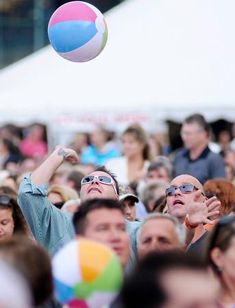 Fans toss around beach balls before the start of the concert.
