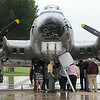 "Visitors take shelter from a rain shower under the wings of the B-17 bomber ""Aluminum Overcast"" during ground tours Tuesday. Photo by Pat Christman"