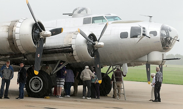"""Visitors take shelter from a rain shower under the wings of the B-17 bomber """"Aluminum Overcast"""" during ground tours Tuesday. Photo by Pat Christman"""