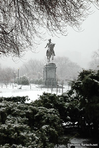 The status of George Washington at the arlington st. enterance of the Boston Public Garden on a snowy day.