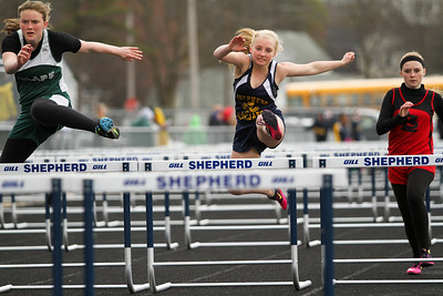 Ken Kadwell/@KenKadwell - Special to the Sun Shepherd freshman Kaitlyn Glowacki, center, competes in the 100 meter hurdles at the Shepherd invitational Friday, May 2, 2014.
