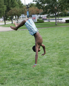Aaron Frost, age 12, of Elyria demonstrates a standing backflip on a grass lot on Park Place Sunday afternoon. photo by Ray Riedel