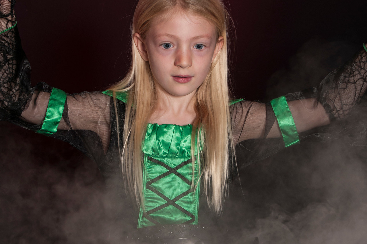 girl dressed as Halloween witch with cauldron solated on dark background