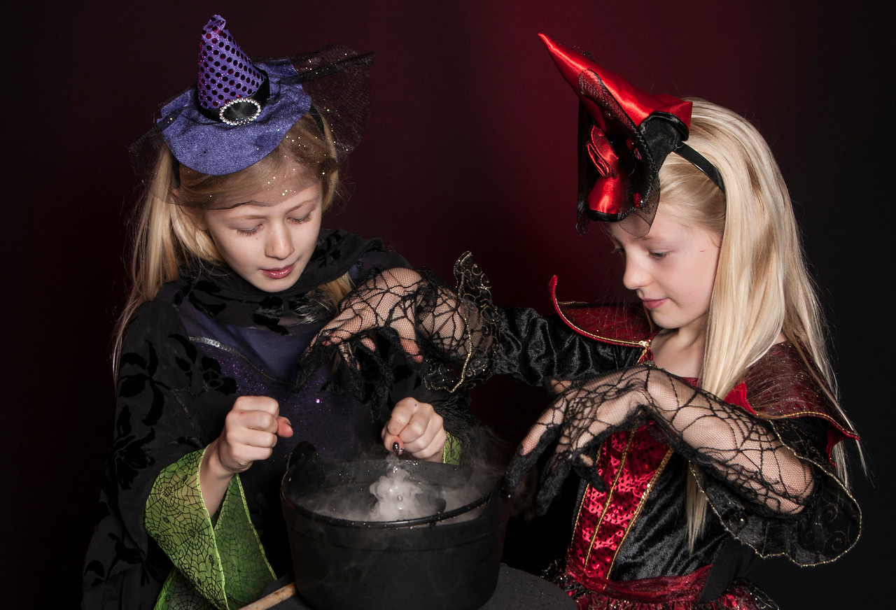 two girls dressed as Halloween witches with a cauldron isolated on dark red background