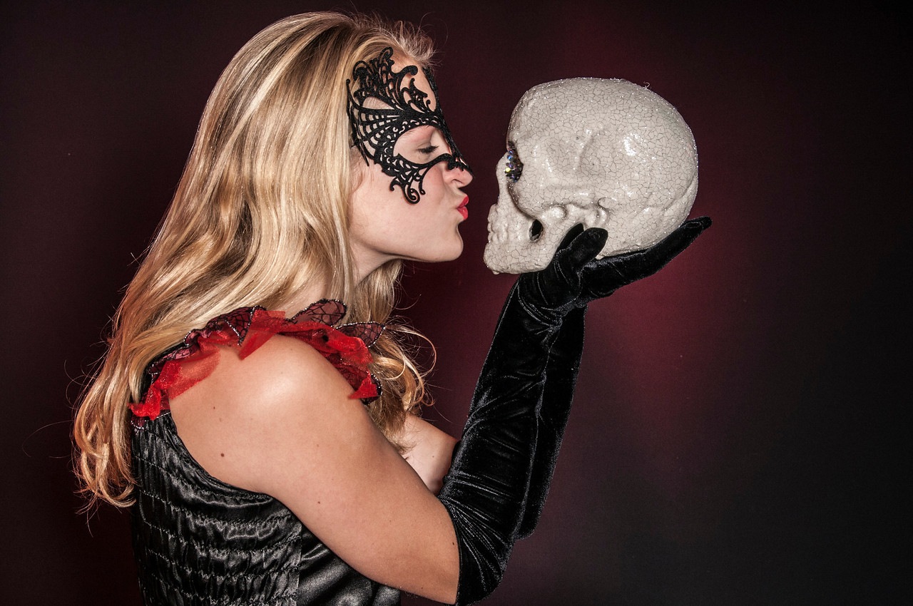 beautiful girl dressed as Halloween witch holding a skull isolated on dark background