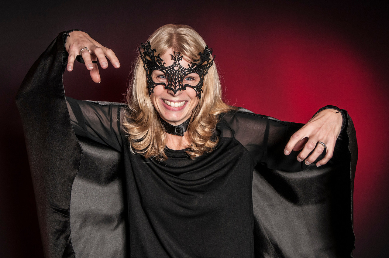 woman dressed as Halloween vampire bat isolated on dark background