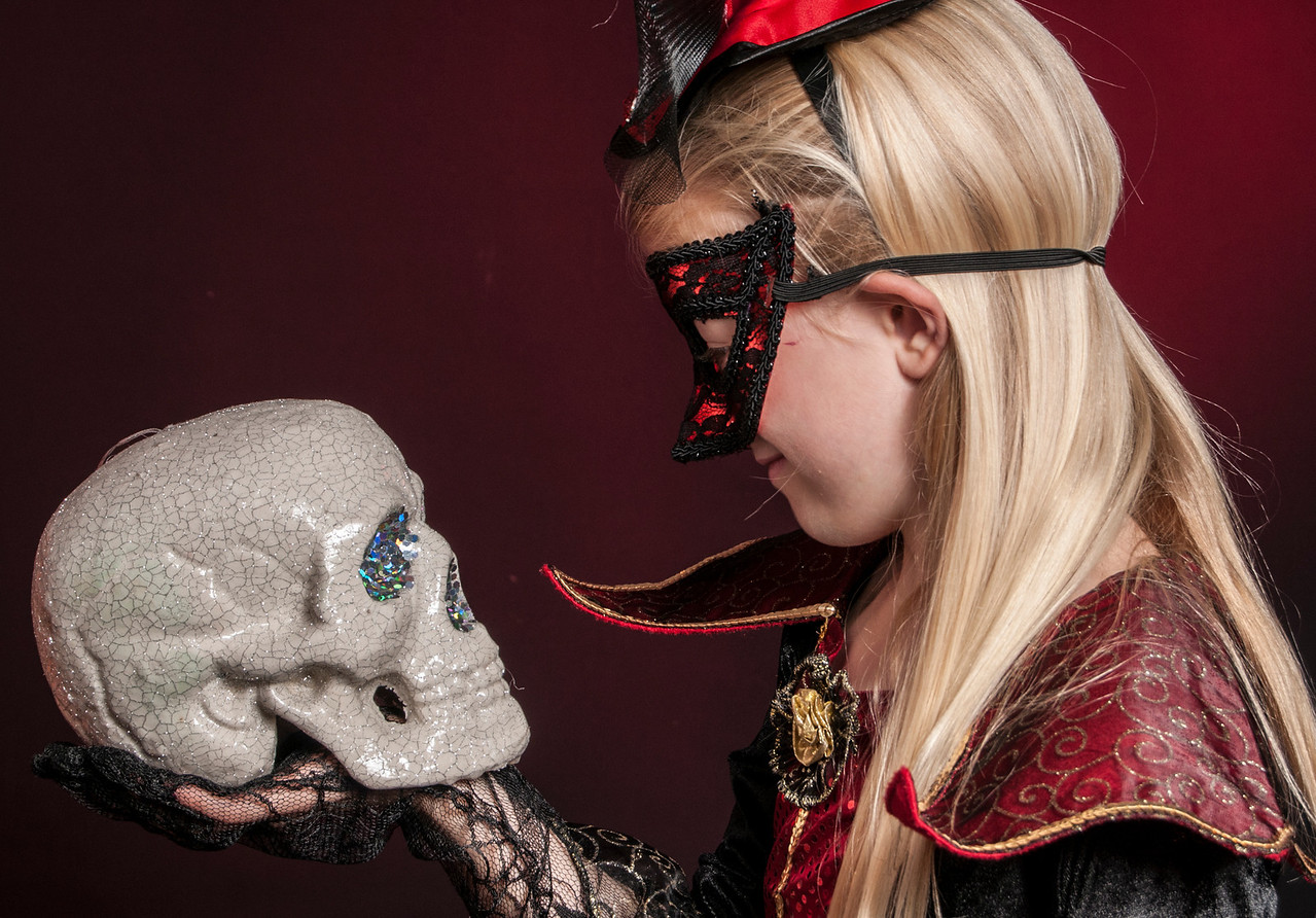 girl dressed as Halloween witch holding a skull isolated on dark red background