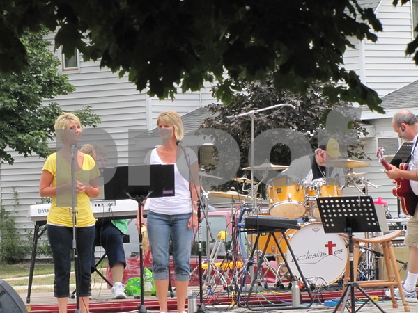 Sisters Lori Tomke and Jenny Larson sing at Badger Lutheran Church's outdoor band concert.