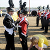 Drum major Hannah Showalter gives out some last minute encouragement as staff members perform emergency pant hemmings.