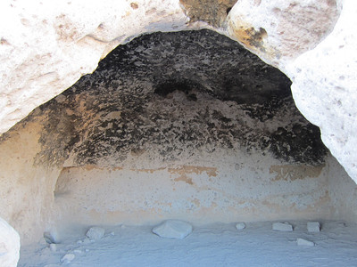 Cave dwelling with fire-blackened ceiling and carved niches. Approximately ten by ten feet.