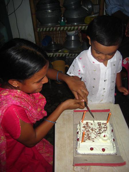 mom and birthday boy cuttinng the cake