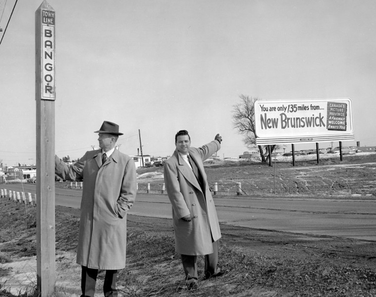 Bangor's outmoded highway sign on outer Hammond Street contrasts with the big oversized billboard pointing tourists toward New Brunswick. The Bangor Jaycees are sponsoring a slogan contest for new promotional signs to be placed along Bangor highways. The program is being carried out in cooperation with Robert H. Patten, left, the city's Industrial Development director. Joseph W. O'Reilly, right, is the chairman of the Jaycee Civic Committee, sponsors of the contest.  BANGOR DAILY NEWS FILE PHOTO BY DANNY MAHER