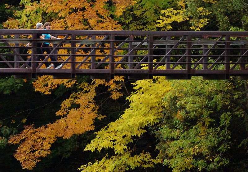 AUTUMN STROLL   Valerie Kitchen (left) and Amy Pozzy walk over the pedestrian footbridge that spans Kenduskeag Stream in Bangor on Tuesday as the fall foliage begins to show its colors. Kitchen and Pozzy are instructors at Valance Pilates Studio on Maine Street in downtown Bangor.  (BANGOR DAILY NEWS PHOTO BY BRIDGET BROWN)<br /> <br /> CAPTION<br /> <br /> Valerie Kitchen (left) and Amy Pozzy walk over the pedestrian footbridge which spans the Kenduskeag Stream in Bangor on Tuesday, Sept. 28, 2010 as the fall foliage begins to show its colors. Both Kitchen and Pozzy are instructors at Valance Pilates Studio on Main Street in downtown Bangor. (Bangor Daily News/Bridget Brown)