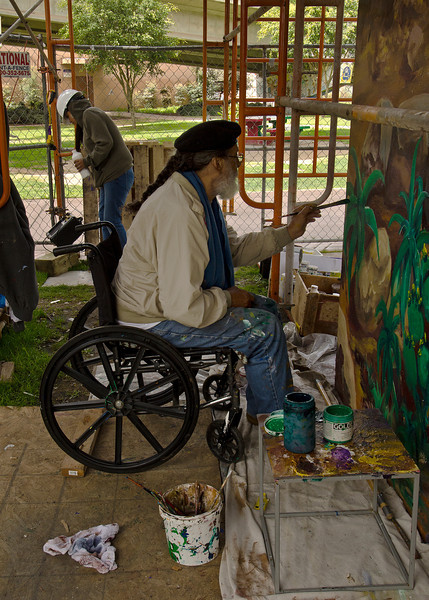 Felipe Adame, artist, finishing up some restoration work on murals first created in 1974