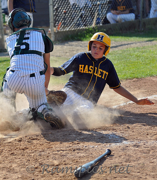Haslett player slides into home plate and the Olivet catcher.