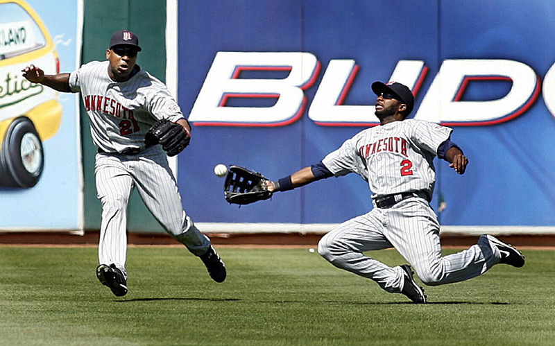 Minnesota Twins' centerfielder Denard Span, right, dives for and catches a fly by the Oakland Athletics' Ryan Sweeney as left fielder Delmon Young closes,  in the fifth inning of an MLB baseball game, Sunday, Aug.31, 2008 in Oakland, Calif.  AP Photo/Dino Vournas