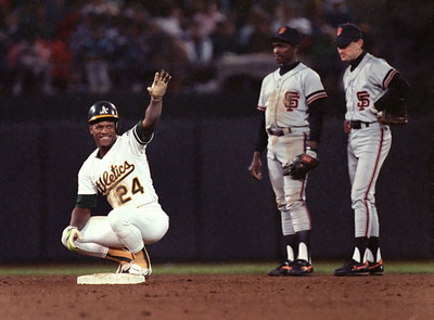 Rickey Henderson of the Oakland A's, with Jose Uribe and Robby Thompson in the background, waves to the crowd following his steal of second base in Game 3 of the 1989 World Series against the San Francisco Giants.  Hayward Daily Review/Dino Vournas