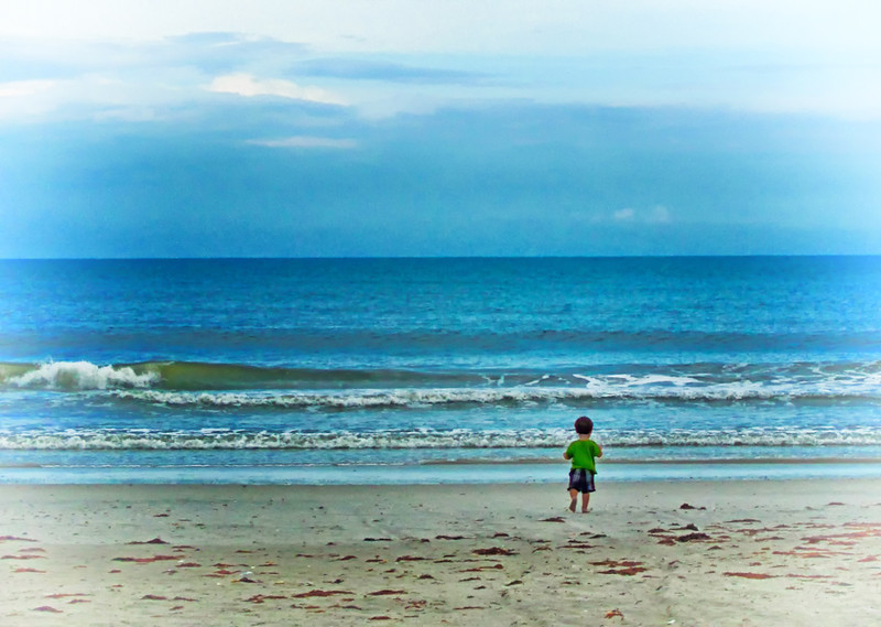Little guy walks toward a huge sea with no trepidation.