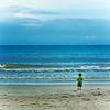 Little guy walks toward a huge sea with no trepidation.