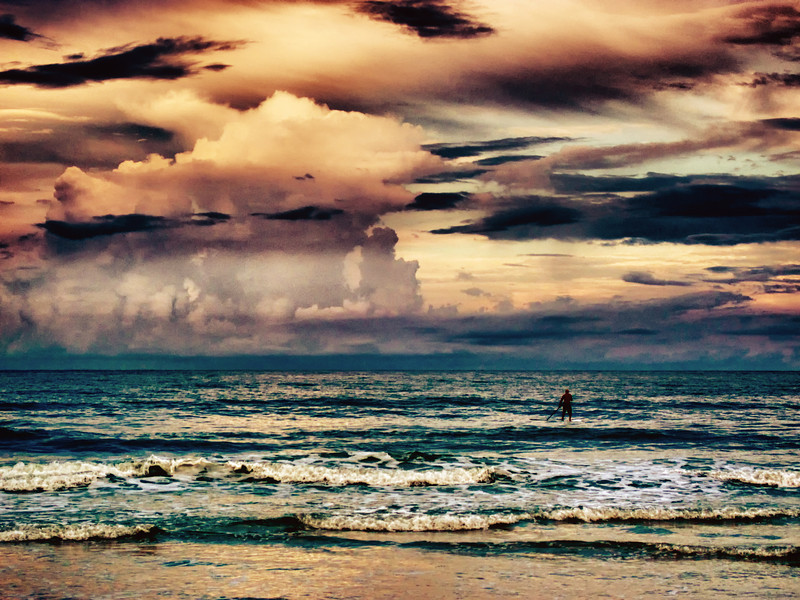 Lone paddle-boarder at sunset
