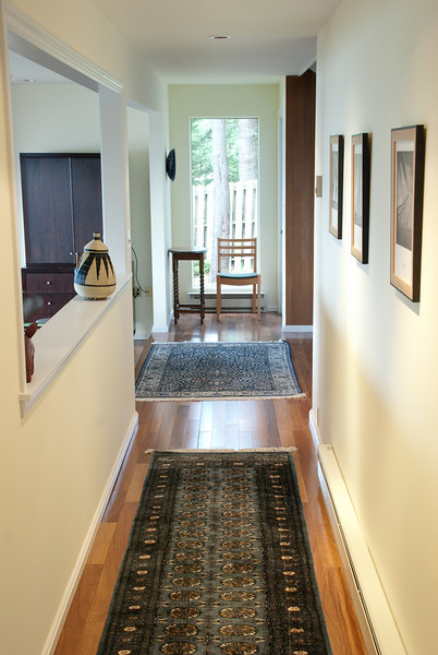 Hallway with window on the left and new floors.