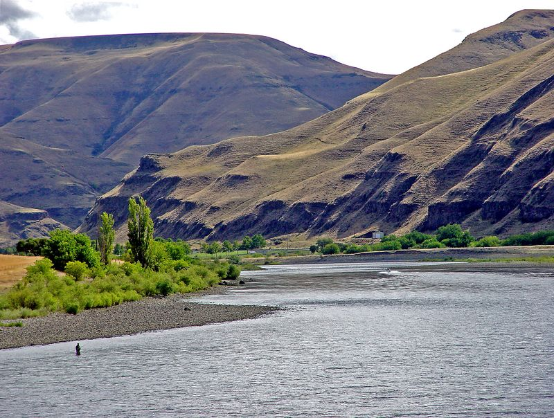 A lone flyfishing steelhead angler is dwarfed by the Snake River environment.