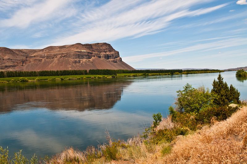 The calm Columbia River flows past the huge promintory cliff a few miles below Wanapum Dam.  Photo taken June 20, 2012