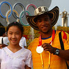Columbian Diego Salazar, silver medalist in weightlifing, poses with a Chinese tourist.