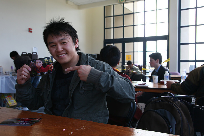 Sammy holds up an Autumn Gem flyer at the Cal Wushu Tournament.