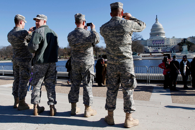 January 20, 2012 - Members of the military pause to take photographs of the West Front of the Capitol building in Washington, D.C. on the day before the 57th Presidential Inauguration. Photo by Billie Weiss.