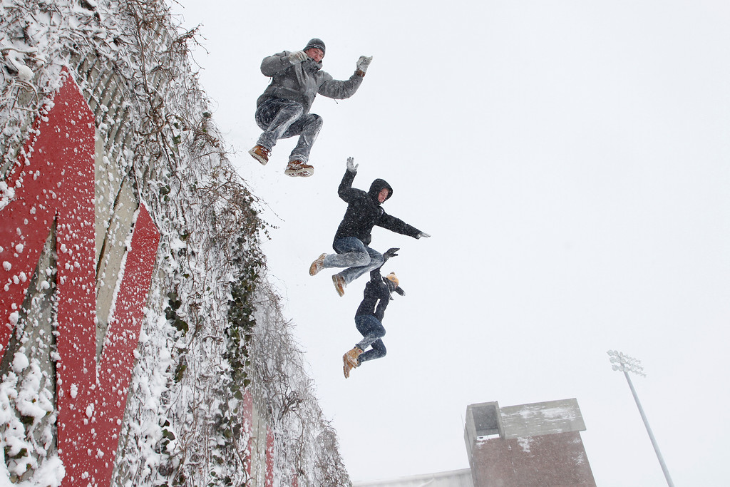 Boston University sophomores Ryan Shea, left, John McKeon and Avery Watterworth jump together onto a snow drift on Nickerson field on Saturday afternoon. (Photo by Michael Cummo)