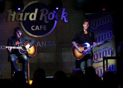 Singer songwriter Rob Thomas, right, performs at Hard Rock Cafe Atlanta in an intimate performance for Q100's Bert Show listeners on Tuesday, Aug. 20, 2009.  Matt Beck, left, if Thomas' bass guitarist.  (AP Photo / Hard Rock International/ Jenni Girtman)