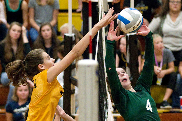 Traverse City Central's Maggie McCrary (8) jumps to block a set from Traverse City West's Brenna Tiernan (4) during the second game at Central High School on Thursday, Sept. 22, 2016. The Titans won in three games.