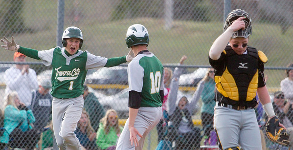 Traverse City West's Sam Clark (1) and Keegan Kenny (10) celebrate winning the game against Traverse City Central, while Central's catcher Griffin Cencer (22) walks off the field at West High School on Tuesday, April 19, 2016. West won the game in the bottom of the seventh inning after Central's pitcher walked in two players.